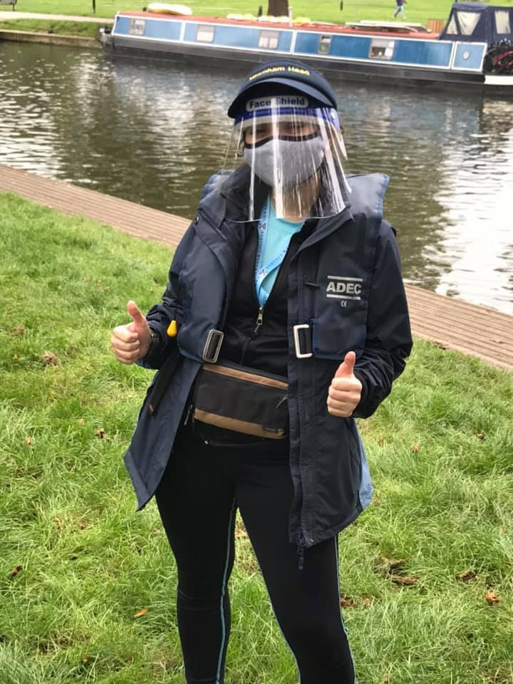 Photo of a person standing by a river, wearing a life jacket and PPE (face mask and face shield)