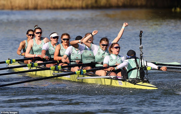 A crew of rowers celebrating at the end of a race
