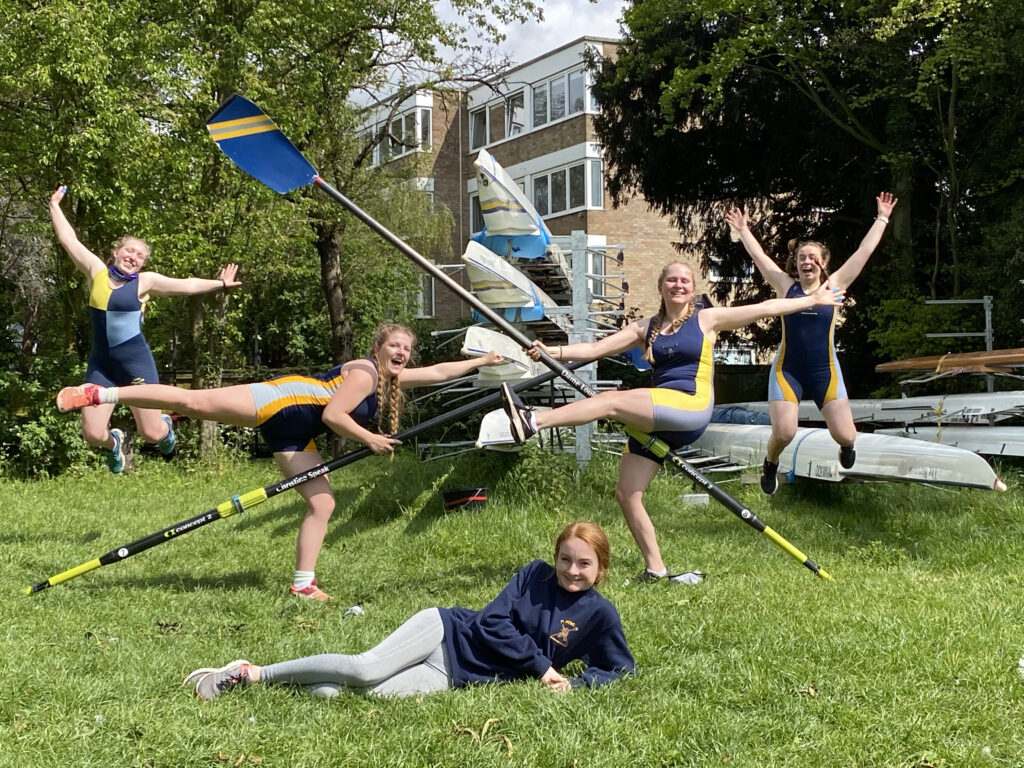 Five people in Newnham College Boat Club kit in celebratory poses in front of a rack of boats
